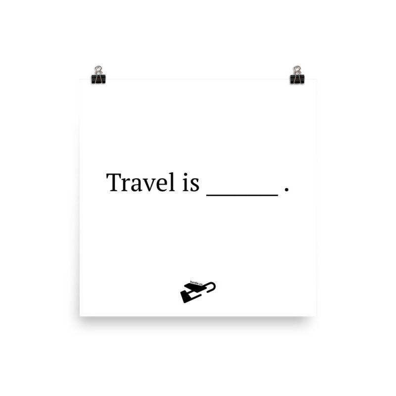 """A white print with two small binder clips on white background, it says """"Travel is [blank]"""" with a plane underneath."""