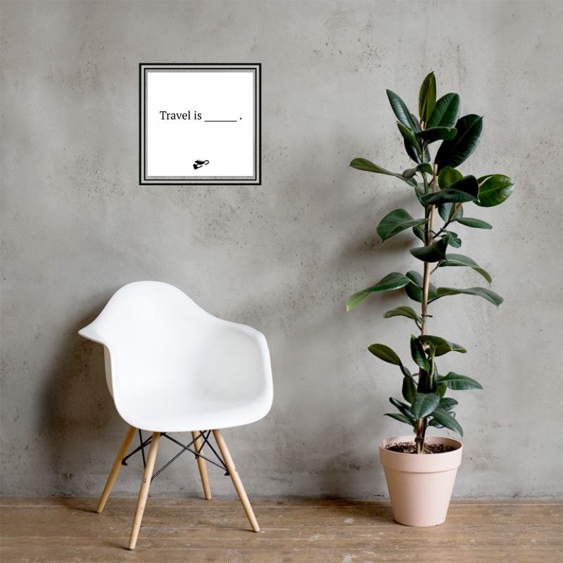 """On a grey wall sits a white framed print with two small binder clips on white background, it says """"Travel is [blank]"""" with a plane underneath."""