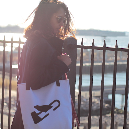 Woman stands in the sun with white burdie tote with black plane logo