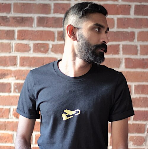 A bearded man models black tshirt with yellow plane logo
