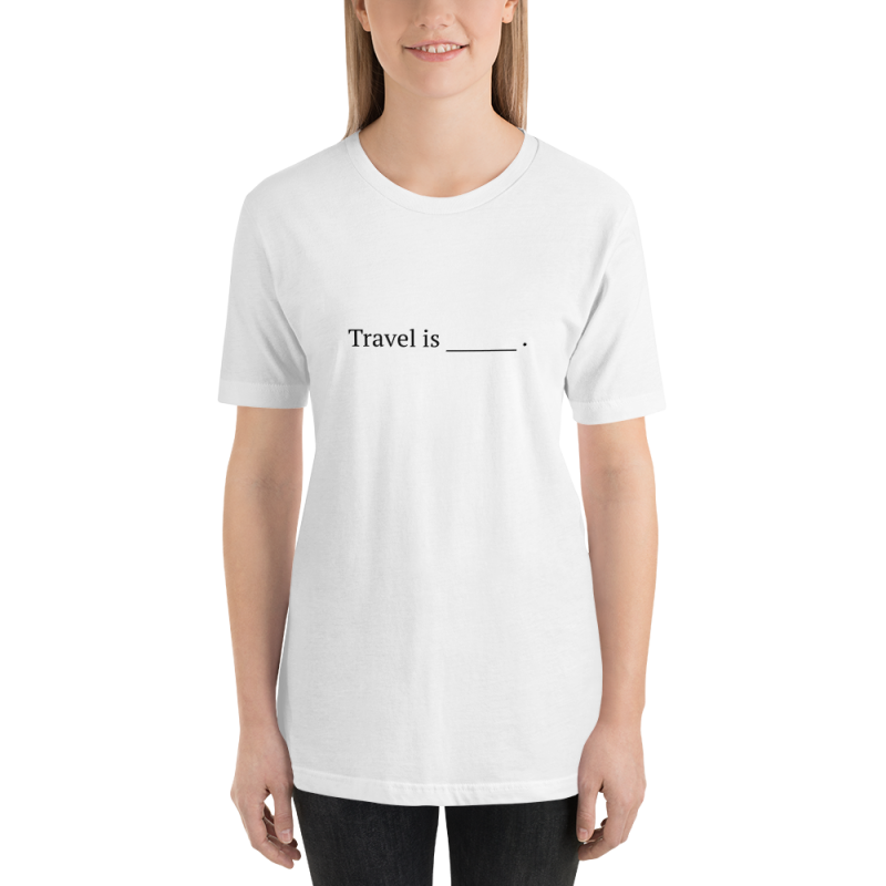"Smiling woman wears white tshirt with ""travel is blank line"" written in black."