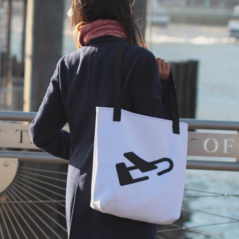 Woman stands by a river with white burdie travel tote with black plane logo