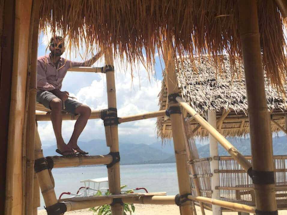 Man sits on bamboo stairs in daytime with the ocean in the background