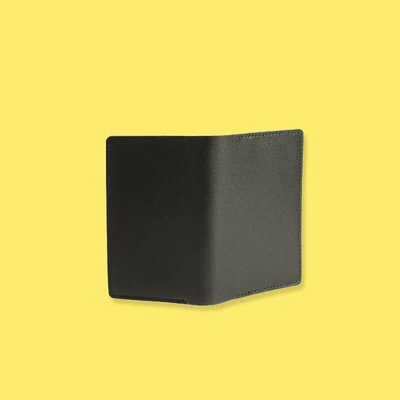 Exterior of black leather passport holder on yellow background