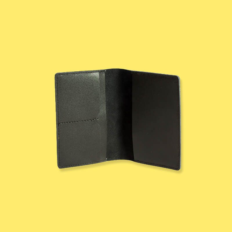 Interior of black leather passport holder on yellow background