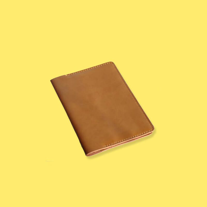 Exterior of light brown leather passport holder on yellow background